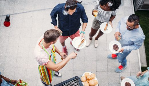Happy Young People Eating and drinking At Barbecue Party. Top view of them standing and drinking near barbecue. Man grilling meat and giving food to his friends.